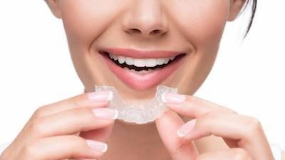 Woman putting in Invisalign | Avondale Dentist